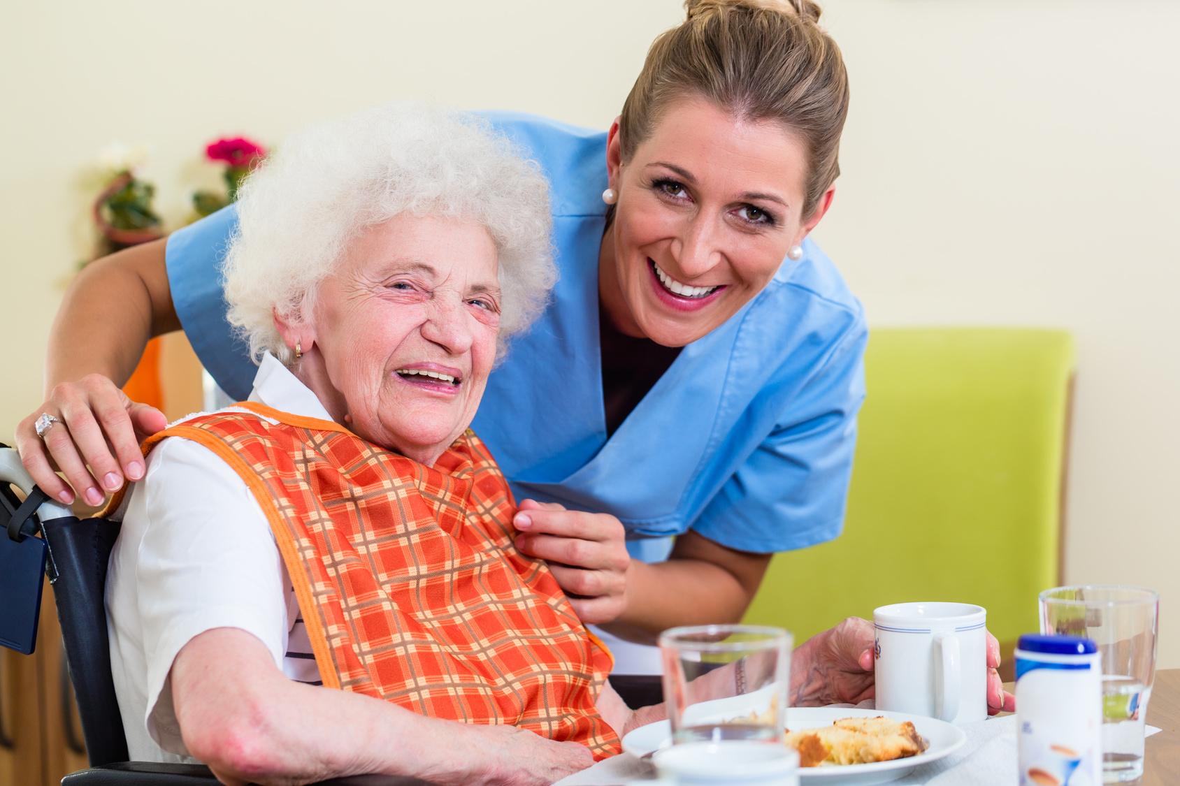 Altenpflegerin lacht mit alter Dame