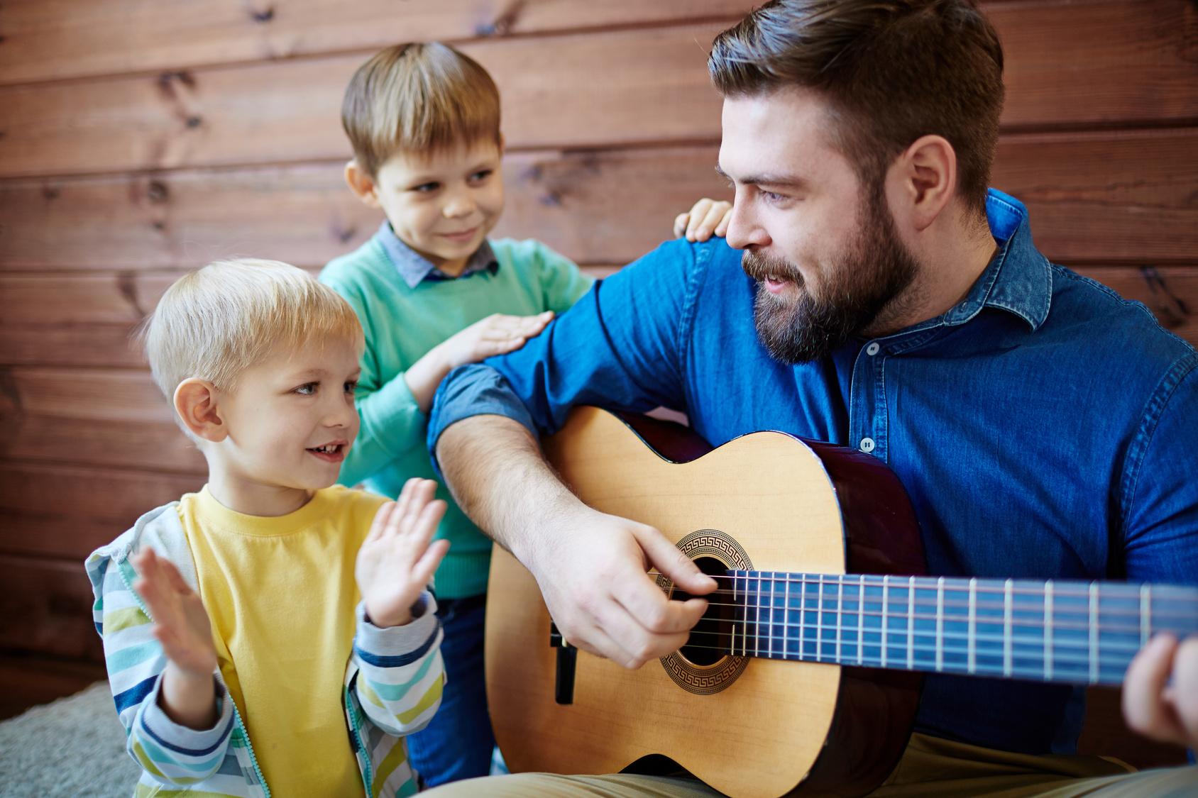Erzieher singt mit zwei Jungen