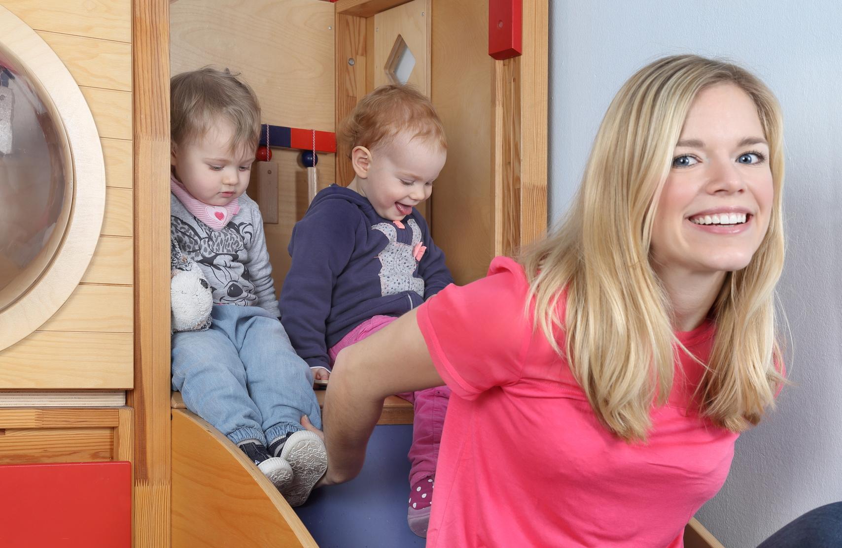 Betreuerin mit zwei Kindern am indoor Spielplatz