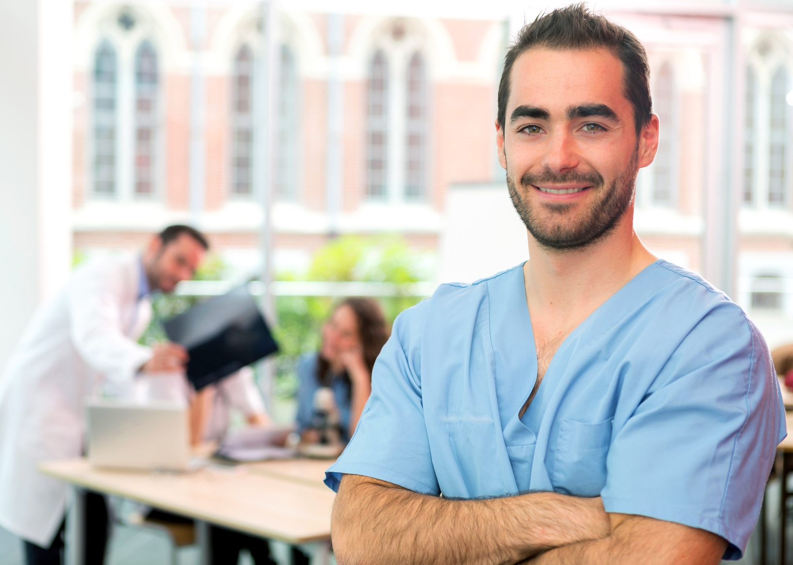 Junger Krankenpfleger, freundlich im Krankenhaus