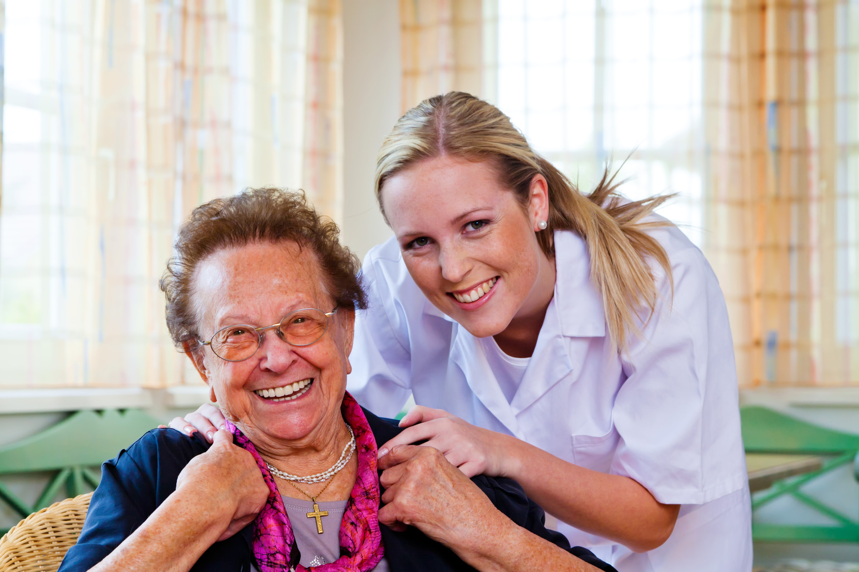 Altenpflegerin fröhlich mit älterer Dame